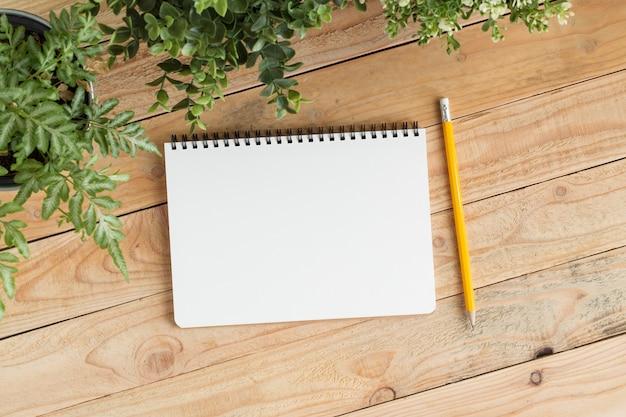 Caderno em branco com e lápis em madeira marrom