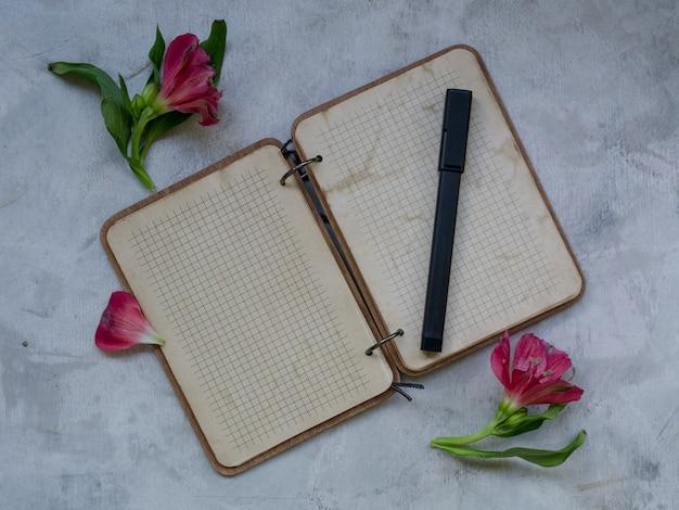 Caderno em branco com flor em fundo cinza.