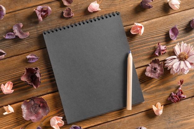 Caderno em branco com flor na mesa de madeira vintage