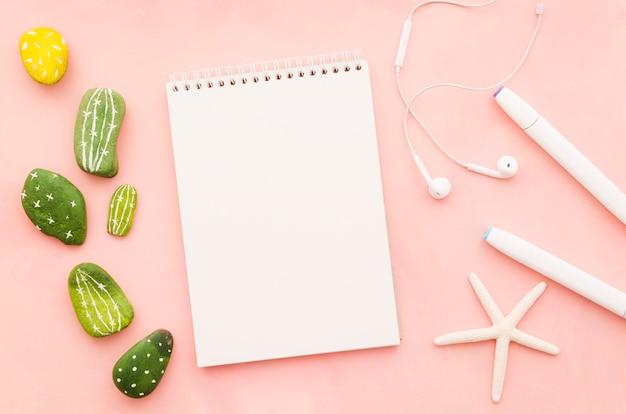 Caderno em branco com fones de ouvido e estrela do mar