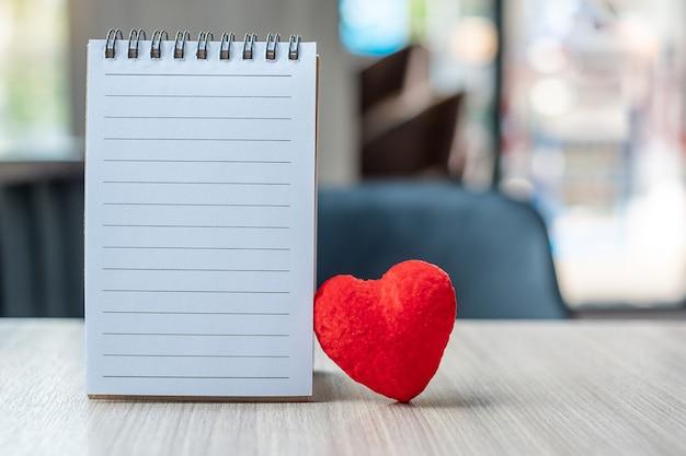 Caderno em branco com forma de coração vermelho