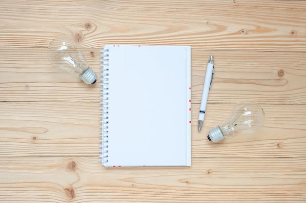 Caderno em branco com lâmpada e papel desintegrado na mesa de madeira