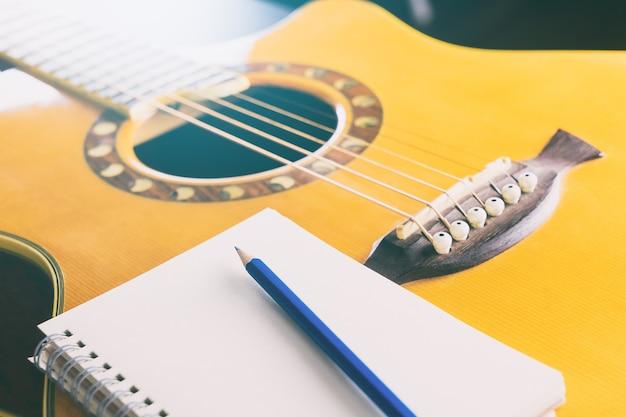 Caderno em branco com lápis e guitarra para composição