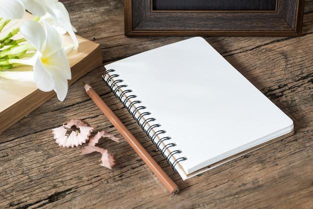 Caderno em branco com lápis na mesa de madeira, conceito do negócio