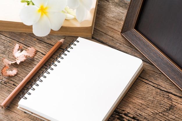 Caderno em branco com lápis na mesa de madeira, negócios