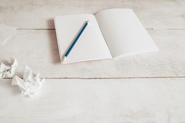 Caderno em branco com lápis na mesa, espaço livre.