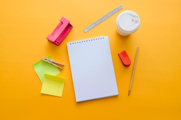 Caderno em branco com objetos criativos em fundo laranja