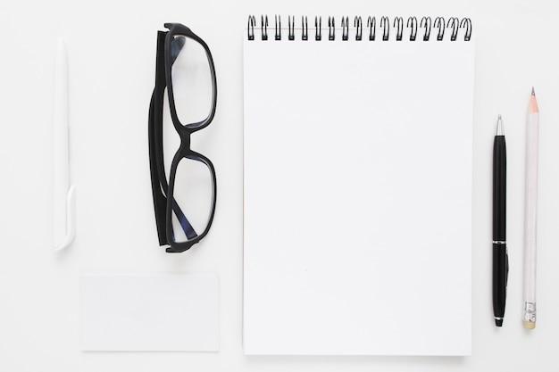 Caderno em branco com papelaria e óculos