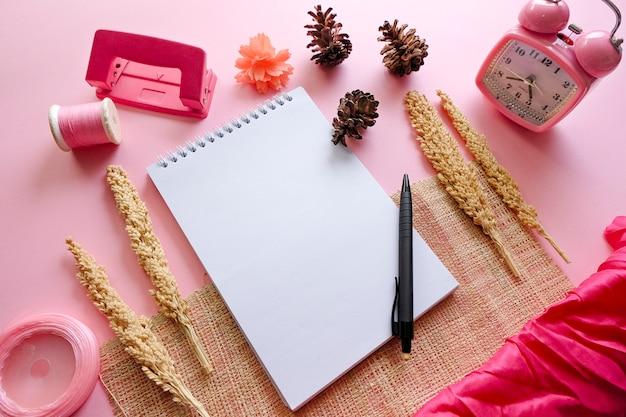 Caderno em branco com pinecoves, weker, perfurador de papel de dois furos