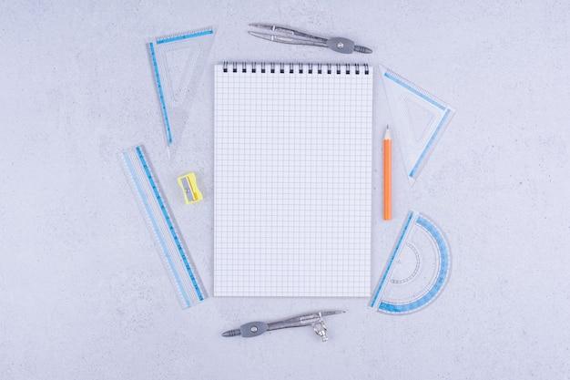 Caderno em branco com régua e canetas ao redor