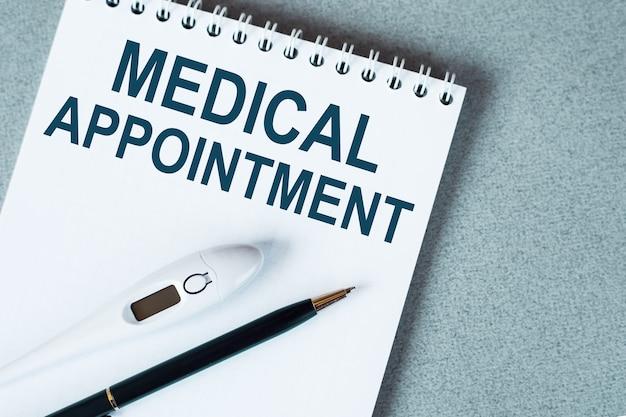 Caderno em branco com termômetro e caneta na mesa. texto de consulta médica.