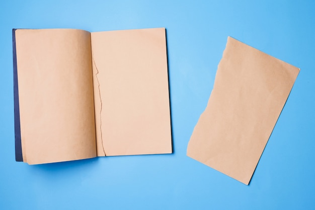 Caderno em branco com um pedaço de papel de nota sobre fundo azul.