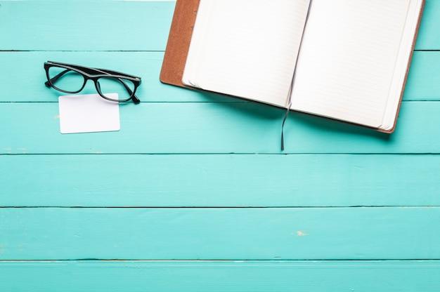 Caderno em branco de cartão em branco e óculos