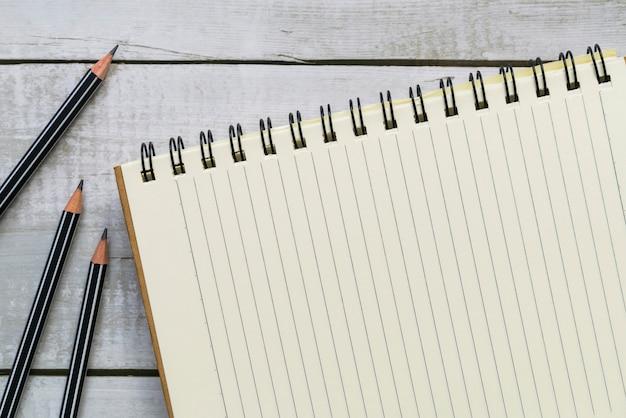 Caderno em branco de vista superior e lápis na mesa de madeira branca com espaço de cópia para negócios e educação
