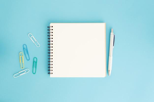 Caderno em branco e caneta azul