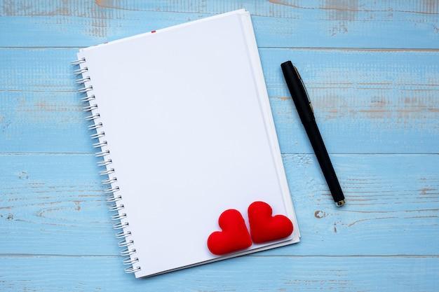 Caderno em branco e caneta com decoração de forma de coração vermelho de casal