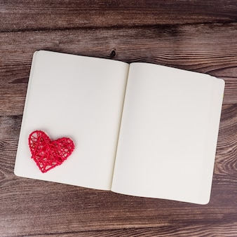 Caderno em branco e caneta com decoração de forma de coração vermelho no fundo da mesa de madeira. casamento, romântico e feliz.