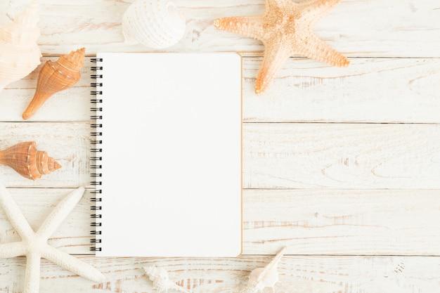 Caderno em branco e conchas no chão de madeira branco
