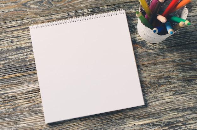 Caderno em branco e conjunto de lápis coloridos em cima da mesa de madeira. fundo de papel.
