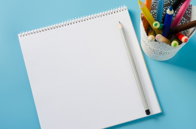Caderno em branco e conjunto de lápis coloridos sobre fundo azul. fundo de papel.