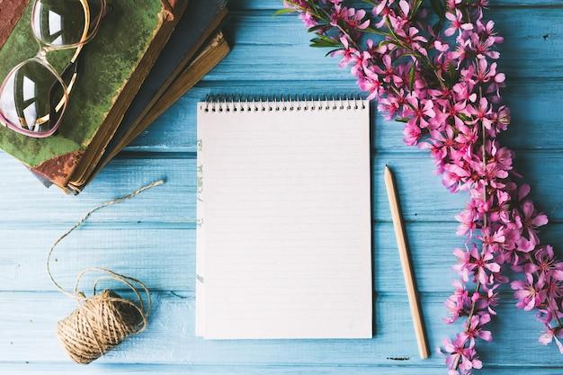 Caderno em branco e flores silvestres sobre fundo azul de madeira. flores do conceito de primavera,