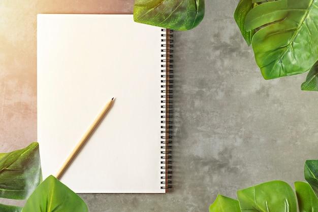 Caderno em branco e folhas verdes