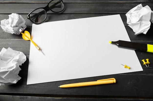 Caderno em branco e lápis com óculos na mesa de madeira