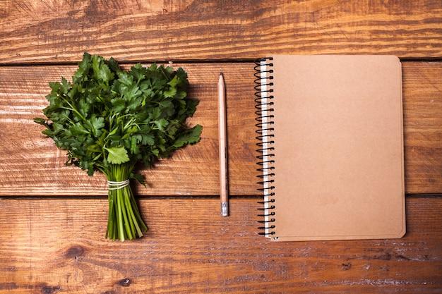 Caderno em branco e lápis com um monte de ervas na mesa de madeira