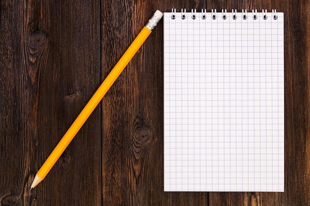 Caderno em branco e lápis em uma mesa de madeira