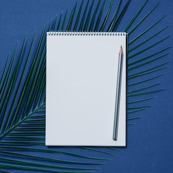 Caderno em branco e lápis sobre fundo azul escuro.