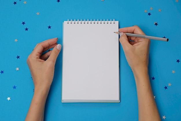 Caderno em branco e mãos femininas com lápis