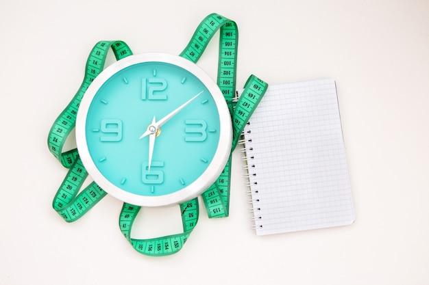 Caderno em branco e relógio