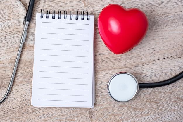 Caderno em branco, estetoscópio com forma de coração vermelho sobre fundo de madeira.