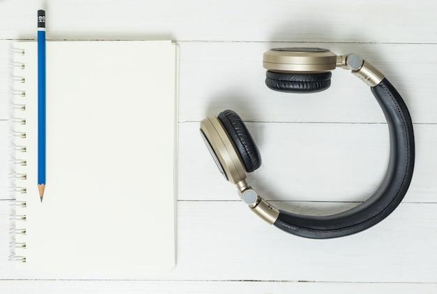 Caderno em branco, lápis e fone de ouvido são as ferramentas para a escrita de música.