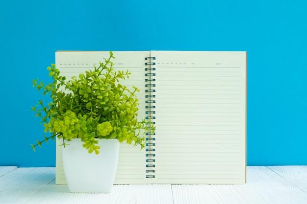 Caderno em branco na frente de mesa de madeira branca azul