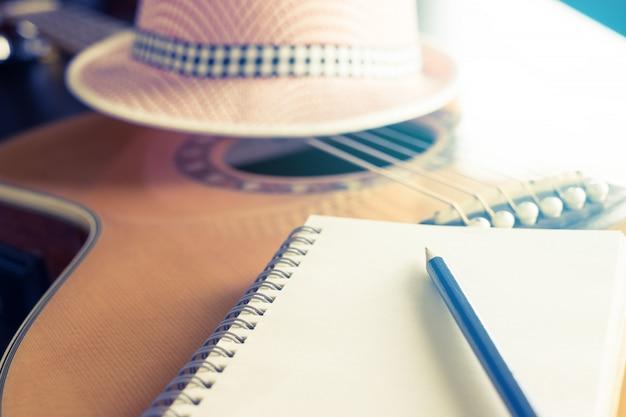 Caderno em branco na guitarra para compositor