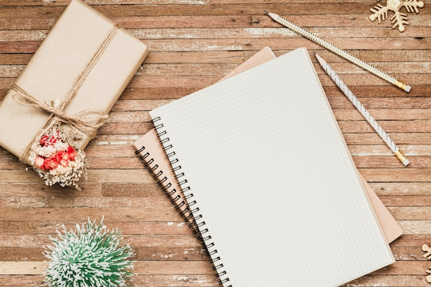 Caderno em branco na madeira com enfeites de natal e caixa de presente