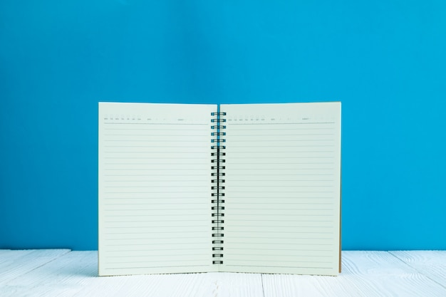 Caderno em branco na mesa de madeira branca frente fundo de parede azul