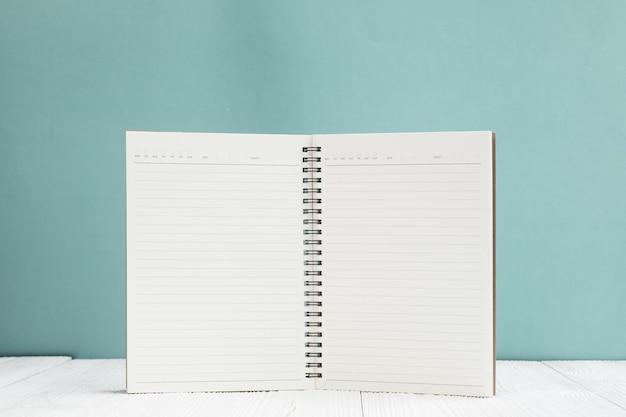 Caderno em branco na mesa de madeira branca frente fundo de parede verde