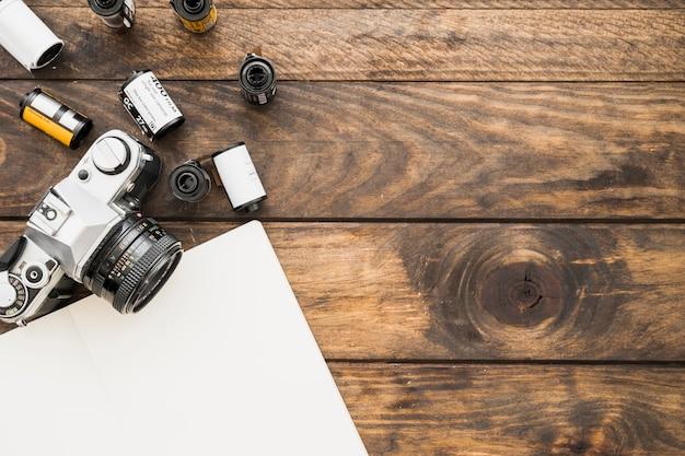 Caderno em branco perto de câmera e cartuchos