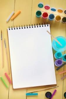 Caderno em branco, pincéis e tintas em fundo amarelo placa de madeira.