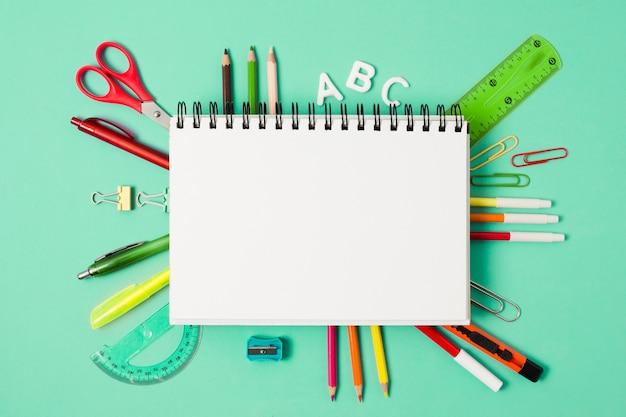 Caderno em branco, rodeado por material escolar de artigos de papelaria