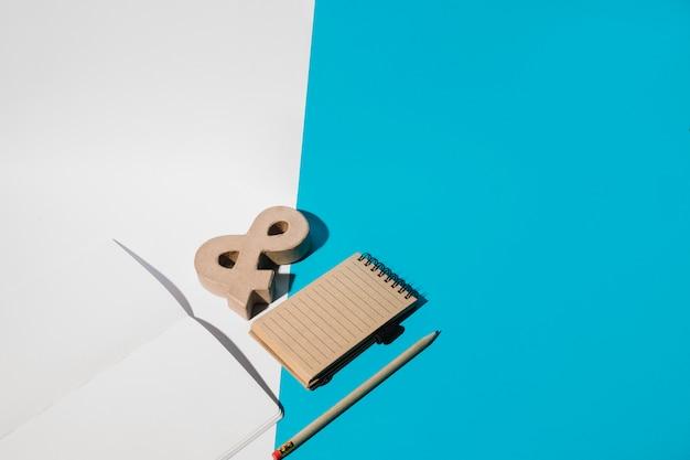 Caderno em branco; símbolo comercial; lápis; e bloco de notas em espiral no papel de parede duplo