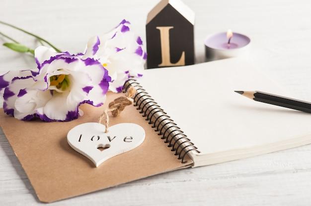 Caderno em branco, velas e flores eustoma