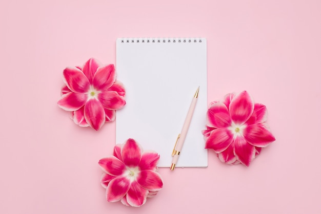 Caderno em espiral com uma folha branca em branco, caneta e flores rosa em uma superfície rosa claro