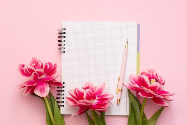 Caderno em espiral com uma folha branca em branco, caneta e tulipas rosa em uma superfície rosa pastel