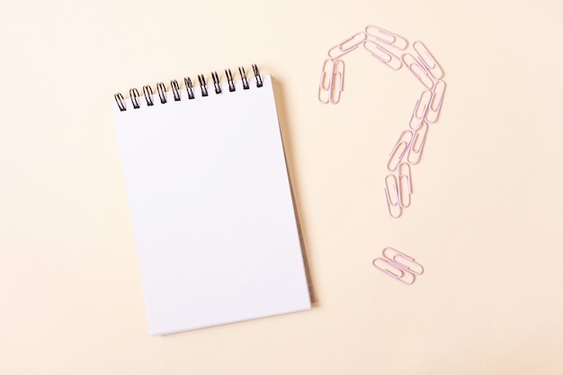 Caderno em espiral e clipes de papel rosa em forma de ponto de interrogação contra um fundo bege