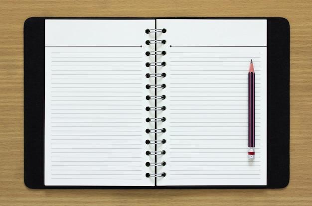 Caderno em espiral em branco e lápis em fundo de madeira