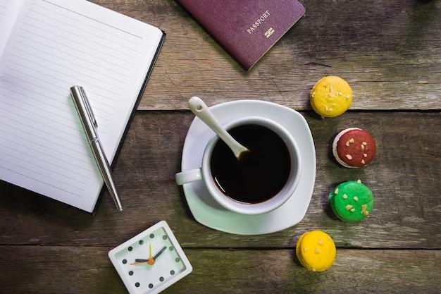 Caderno em madeira rústica com biscoito e xícara de café e passaporte e relógio