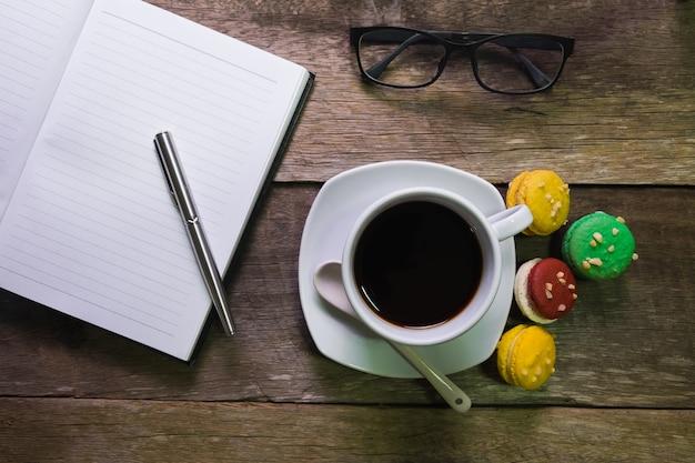 Caderno em madeira rústica com copo de café e óculos de macaroon